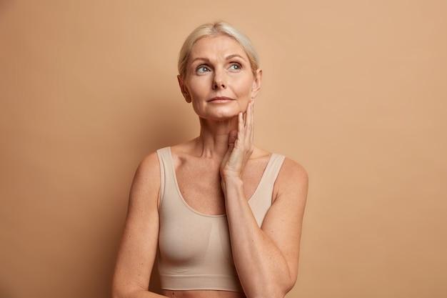 Frau berührt die haut, nachdem sie die oben konzentrierte anti-age-creme mit nachdenklichem ausdruck aufgetragen hat, trägt ein abgeschnittenes oberteil isoliert auf braun
