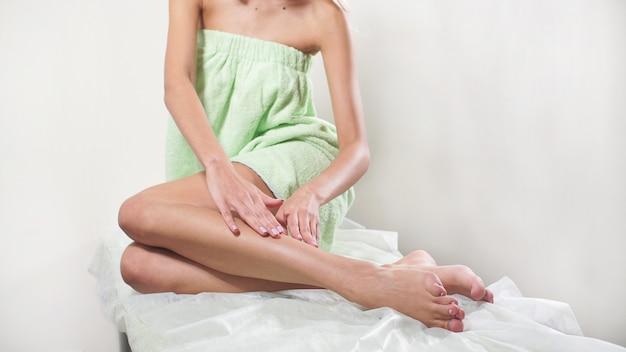 Frau berührt ihre sexy langen beine. körperpflegekonzept