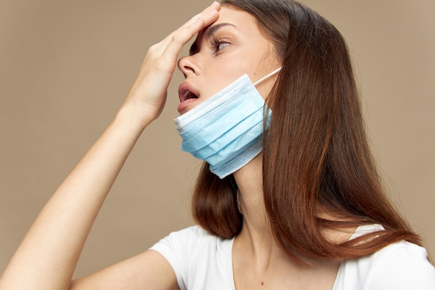 Frau berührt ihren kopf mit der hand und einer medizinischen maske auf einem weißen t-shirt modell gesicht
