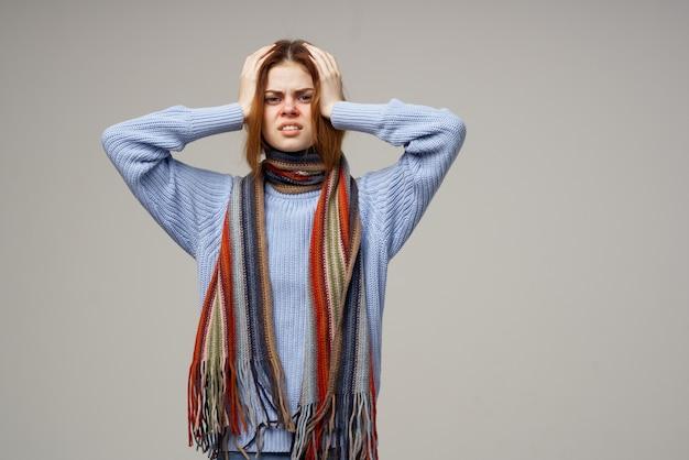 Frau berührt ihren kopf mit ihren händen gesundheitsprobleme warme kleidung schal kopfschmerzen. hochwertiges foto