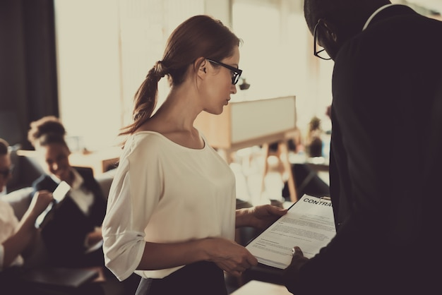 Frau besprechen vertragsbedingungen mit kollegen im büro.