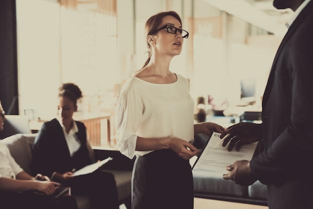 Frau besprechen vertragsbedingungen mit kollegen.