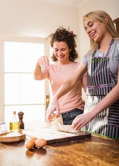 Frau besprühen mehl auf dem teig, der zu hause von ihrer freundin geknetet wird