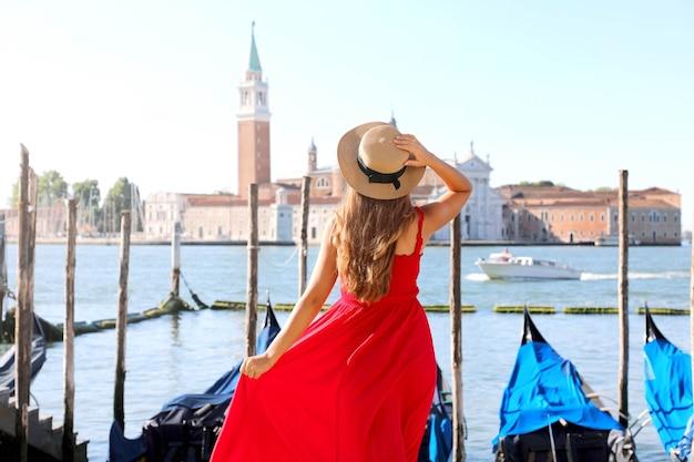 Frau besucht venedig in italien. hintere ansicht der schönen jungen frau im roten kleid, die ansicht der venezianischen lagune genießt.