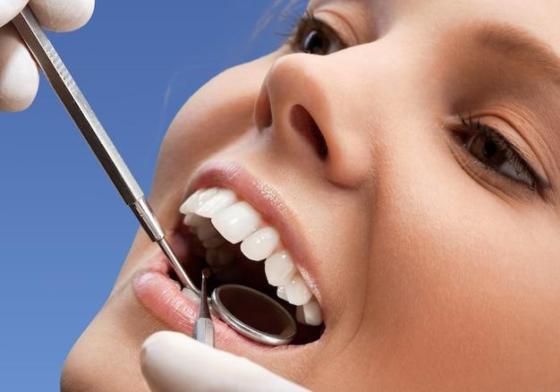 Frau besucht zahnarzt, zeigt zähne
