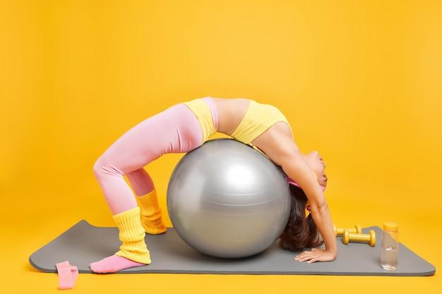Frau beugt sich über fitnessball hat sportliche figurübungen auf karemat in abgeschnittenem oberteil und leggings führt aktiven lebensstil macht regelmäßiges training