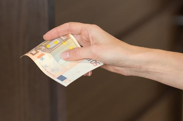 Frau bezahlt das frühstück im café mit 50-euro-banknoten bar.