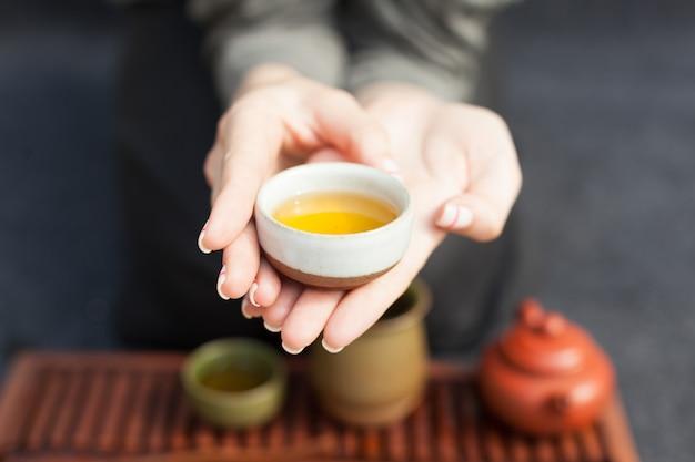 Frau bietet heißen tee in einer vintage keramikschale an.