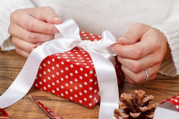 Frau bindet einen bandbogen auf ein eingewickeltes geschenk nahaufnahme