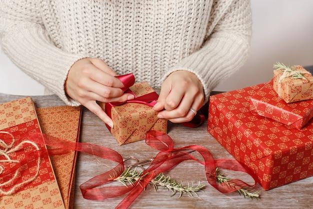 Frau bindet einen bandbogen und verpackt geschenke nah oben