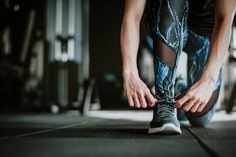 Frau bindet ihre Schnürsenkel vor dem Training