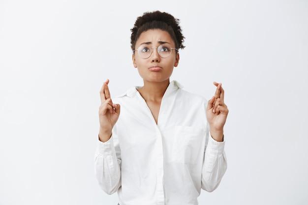 Frau bittet gott um erfüllung des traums. porträt einer nervösen bettelnden verärgerten frau in brille und weißem hemd, die aufschaut, lippen spitzt und daumen drückt, um zu beten, an wunder zu glauben, während sie hofft
