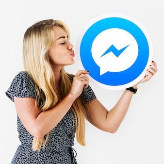 Frau bläst einen kuss auf ein facebook-messenger-symbol