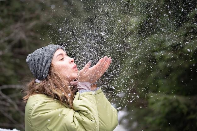 Frau bläst schnee im freien auf winterhintergrundglück und freudekonzept