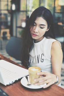 Frau blickt auf eine glas-vase mit kaffee