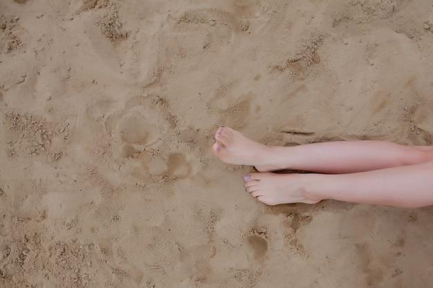 Frau bräunte beine, strohhut und tasche auf sandstrand. mit den füßen im sand am strand entspannen.