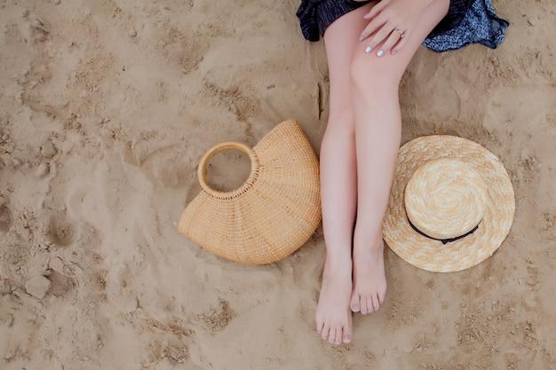 Frau bräunte beine, strohhut und tasche auf sandstrand. reise-konzept. mit den füßen im sand am strand entspannen.