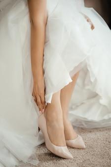 Frau braut begradigt schuhe mit hand sitzen
