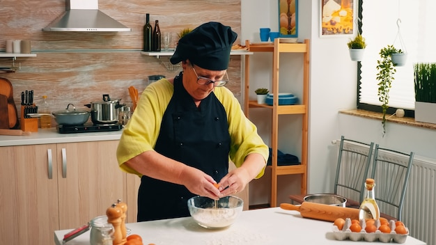 Frau bricht ei über mehl und macht teig für backwaren. älterer konditor, der eier auf glasschüssel für kuchenrezept in der küche knackt, von hand mischt, zutaten knetet und hausgemachten kuchen zubereitet