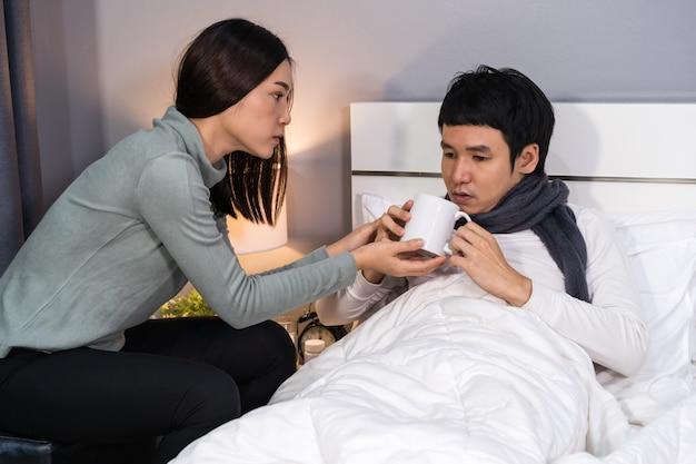 Frau bringt eine tasse heißes wasser und gibt ihrem kranken mann zu hause auf dem bett trinken