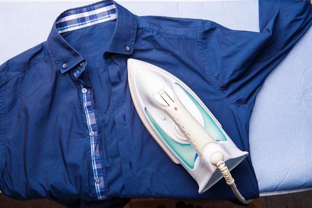 Frau bügelt das hemd des mannes. ansicht von oben. konzept der hausarbeit.