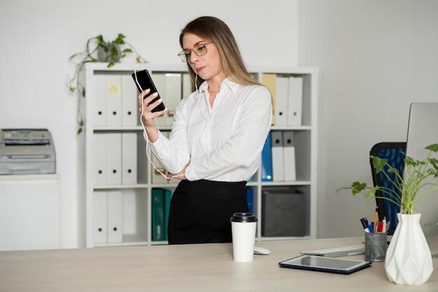 Frau checkt ihr handy bei der arbeit