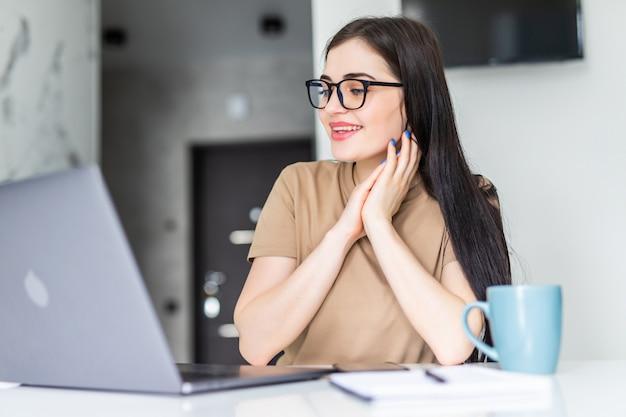 Frau checkt morgens ihre e-mails auf einem laptop, während sie kaffee trinkt