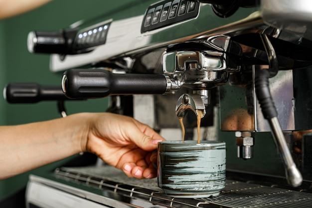 Frau coffeeshop-arbeiter, der kaffee auf professioneller kaffeemaschine nah herauf bereitet