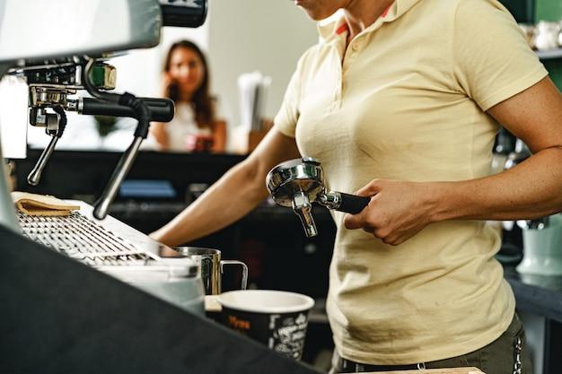 Frau coffeeshop-arbeiter, der kaffee auf professioneller kaffeemaschine vorbereitet