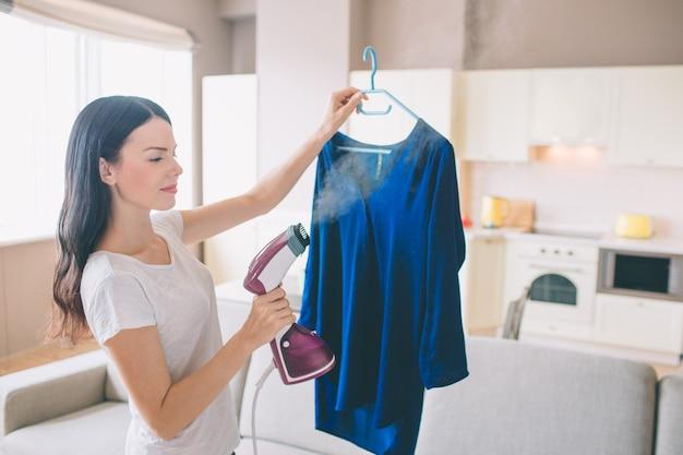 Frau dampft blaues hemd im raum. sie hält ein kleines eisen in der hand. brünette konzentriert sich auf die arbeit.