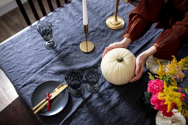 Frau deckt den tisch am vorabend der herbstferien