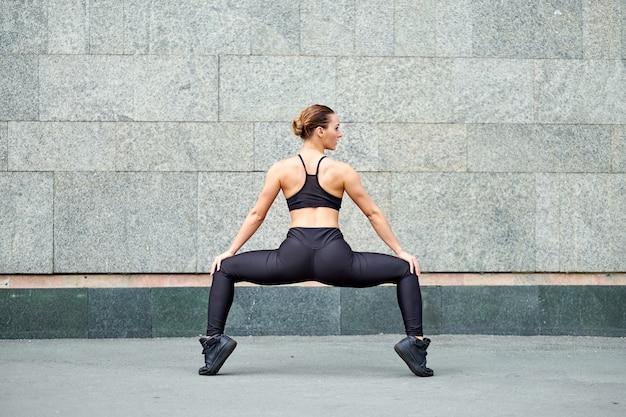 Frau dehnen. fitness oder turner oder tänzer, die übungen auf grauem wandhintergrund machen