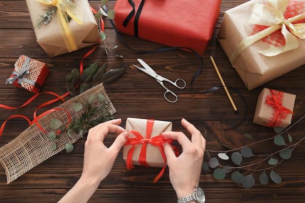 Frau dekoriert geschenkbox auf dem tisch
