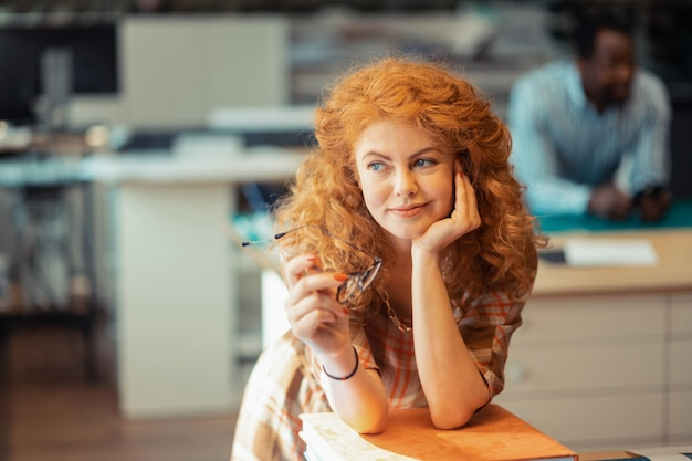 Frau denkt. schöne blauäugige frau mit lockigem haar, die über persönliche dinge nachdenkt