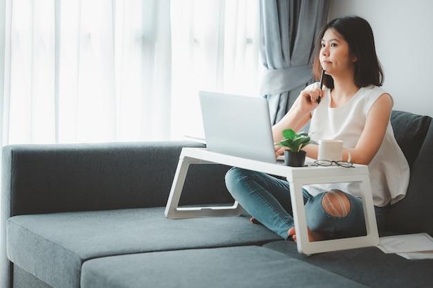 Frau denkt, während zu hause auf sofa arbeiten