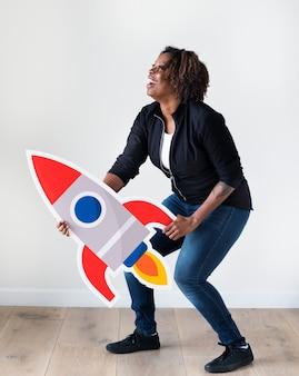 Frau der afrikanischen abstammung, die rocketship ikone hält