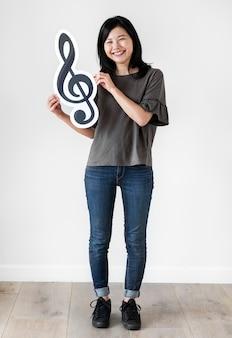 Frau der asiatischen ethnie, die eine ikone der musikalischen anmerkung hält
