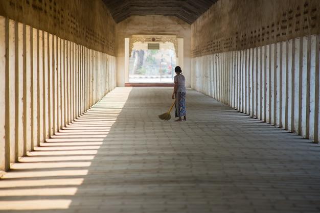 Frau der buddhismus-pilgerfahrtzeremonie mit den besen, die am gehweg shwezigon pagode fegen