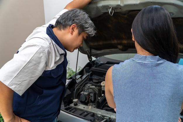 Frau, der das auto gehört, steht und sucht nach dem mechaniker. überprüfen sie den motor, um die ursache zu finden