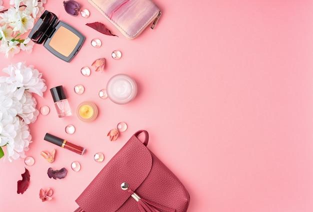 Frau der flachen lage frau mit kosmetik, gesichtscreme, tasche, blumen auf hellrosa tabelle
