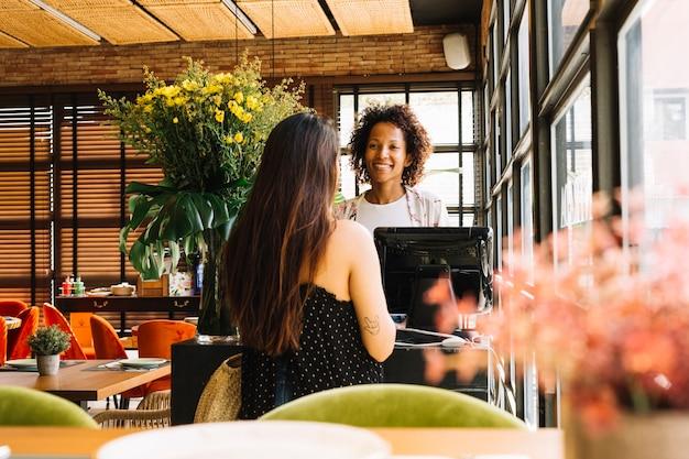 Frau der hinteren ansicht, die vor dem jungen weiblichen kassierer steht, der am bargeldschreibtisch im café arbeitet