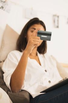 Frau der jungen frau des mittelschusses, die eine bankkarte betrachtet