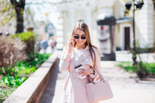 Frau der oberschicht. moderne frau, die draußen simst. modefrau in einer sonnenbrille und in einer rosa jacke mit kaffee
