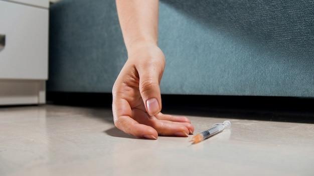 Frau der toten frau mit drogensucht, die mit spritze auf dem boden liegt.
