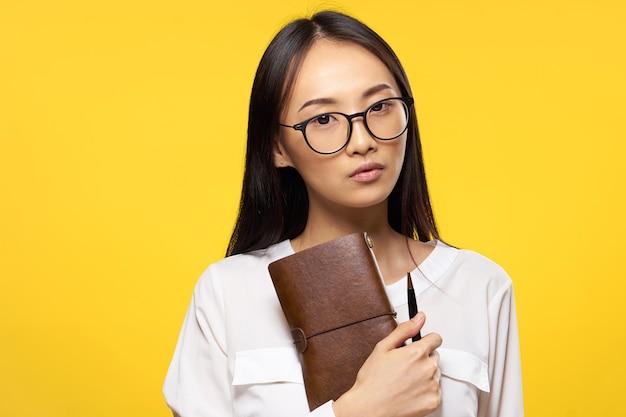 Frau des asiatischen aussehens mit notizblock in händen und stiftbrille elegante stilarbeit