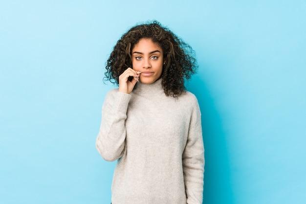 Frau des gelockten haares des jungen afroamerikaners mit den fingern auf den lippen, die ein geheimnis halten.