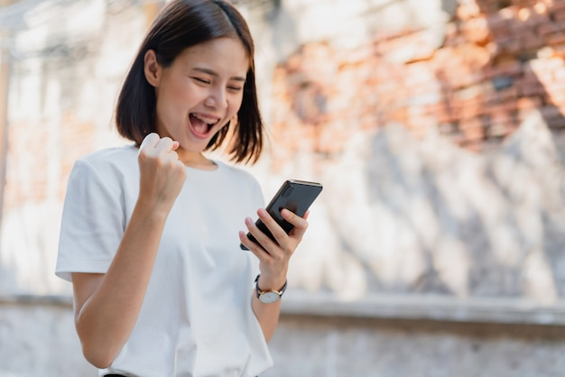 Frau des glücklichen lächelns und des haltens des intelligenten telefons mit überrascht für erfolg.