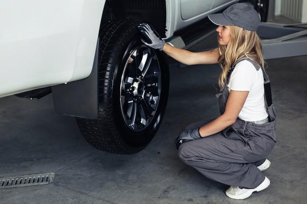 Frau des hohen winkels, die auto am service repariert