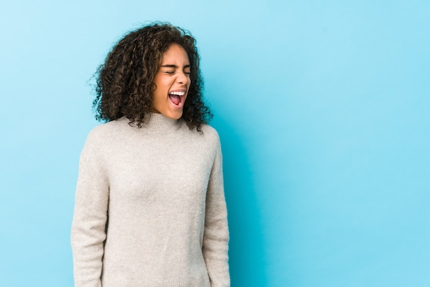 Frau des lockigen haares des jungen afroamerikaners, die in richtung zu einem kopienraum schreit