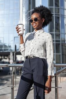 Frau des niedrigen winkels im sonnenlicht, die kaffee trinkt